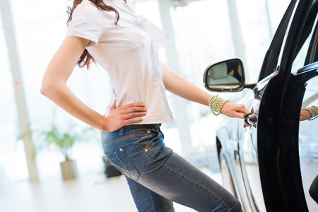 woman opens the door to a new car, car inspection in the showroom