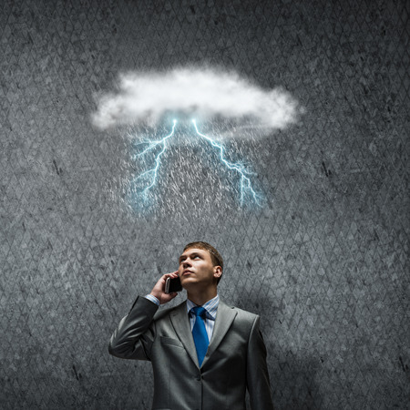 Young businessman looking above at raining sky