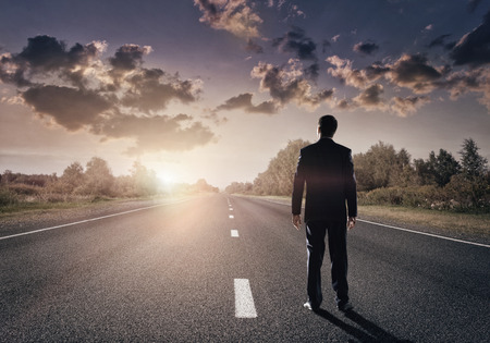 Businessman goes straight on his way on asphalt road