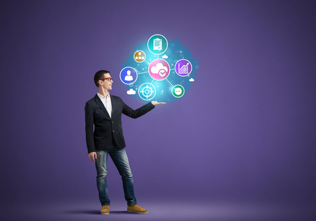Photo for Young man presenting in hand social networking icons on color background - Royalty Free Image