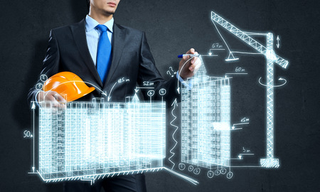 Photo pour Young man engineer drawing sketches of construction project - image libre de droit