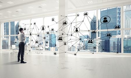 Photo pour Elegant businessman in 3D office interior and social connection concept. Mixed media - image libre de droit