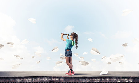 Photo pour Cute kid girl standing on house roof and looking in spyglass - image libre de droit