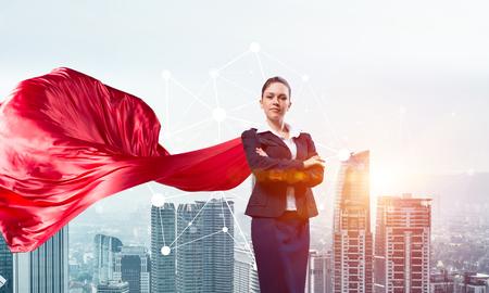 Foto de Young confident businesswoman wearing red cape against modern city background - Imagen libre de derechos