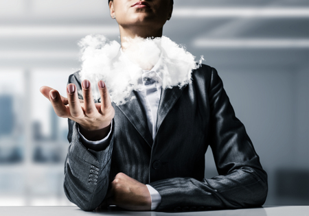 Closeup of business woman in suit presenting white cloud in her palm with office view on background.