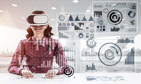 Photo pour Portrait of beautiful and young woman in checkered shirt using virtual reality goggles and interracting with digital media interface while sitting inside bright office building. - image libre de droit