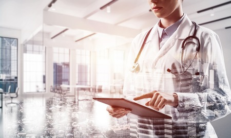 Foto de Young female doctor in white sterile coat touching tablet screen while standing at hospital building. Digital technologies for medical employee. Double exposure - Imagen libre de derechos
