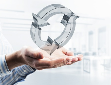 Photo pour Close of businessman holding in palm reload glass icon. Mixed media - image libre de droit