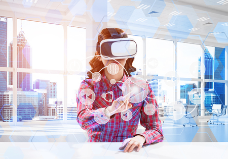 Photo pour Horizontal shot of young and beautiful woman in checkered shirt using virtual reality headset and media interface while sitting inside bright office building. - image libre de droit