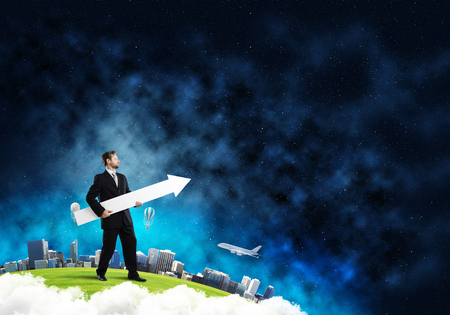 Photo pour Conceptual image of young successful business man in suit pointing aside by means of big white banner in form of arrow while standing on Earth globe. - image libre de droit