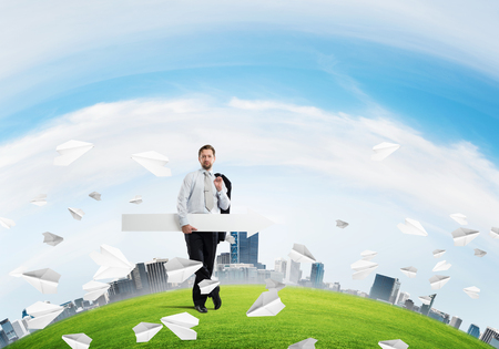 Confident businessman holding jacket behind his back in one hand and white big arrow in another hand while standing among flying paper planes at green meadow and cityscape view on background.
