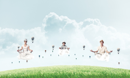 Photo pour Young family keeping eyes closed and looking concentrated while meditating on clouds among flying aerostats with bright and beautiful landscape on background. - image libre de droit