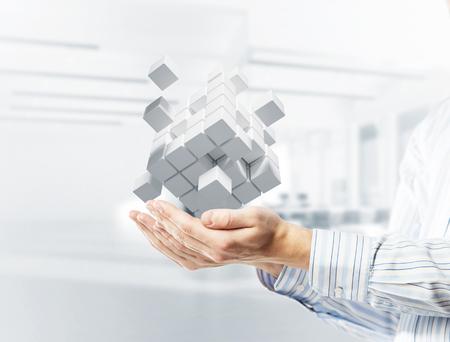 Foto de Close of businessman hand holding cube figure as symbol of innovation. 3D rendering - Imagen libre de derechos