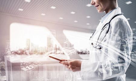 Foto de Double exposure of confident female doctor in white coat standing at hospital building with laptop in hands and cityscape view. Modern gadgets for medical industy employee - Imagen libre de derechos