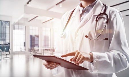 Foto de Close up conceptual image of young medical industry employee touching screen of tablet while standing inside white hospital building. Woman doctor with modern gadget in hands - Imagen libre de derechos