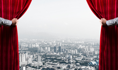 Photo pour Hands of businessman opening red velvet curtain and cityscape at background - image libre de droit