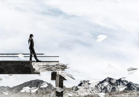 Photo pour Businessman walking blindfolded on concrete bridge with huge gap as symbol of hidden threats and risks. Skyscape and nature view on background. 3D rendering. - image libre de droit