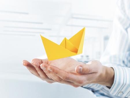 Photo pour Close of businessman hands holding paper ship as symbol for success. Mixed media - image libre de droit