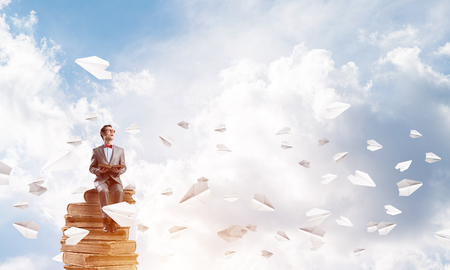 Photo pour Funny man in red glasses and suit sitting on book and paper planes flying around - image libre de droit