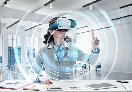 Foto de Horizontal shot of beautiful and young business woman in suit using virtual reality headset with digital security interface while standing inside office. - Imagen libre de derechos