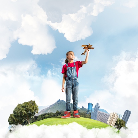 Photo pour Cute kid girl on city floating island playing with retro plane model - image libre de droit