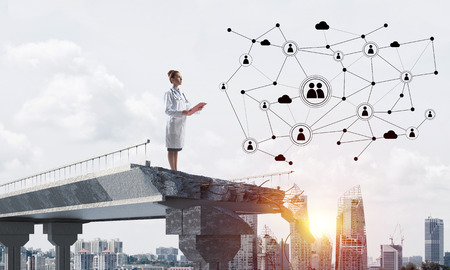 Photo for Young woman doctor in white medical suit studying social network structure while standing at the end of broken bridge. Cityscape view on background - Royalty Free Image