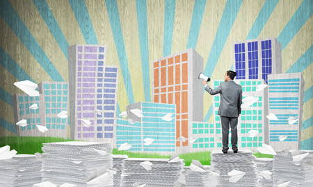 Foto de Businessman in suit standing among flying paper planes with speaker in hand with sketched cityscape view on background. Mixed media. - Imagen libre de derechos