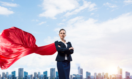 Foto de Young confident businesswoman wearing red cape against modern city background - Imagen libre de derechos