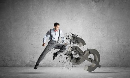 Photo pour Young furious businessman jumping and crashing with kick stone dollar symbol - image libre de droit