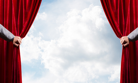 Photo for Human hand opens red velvet curtain on blue sky background - Royalty Free Image