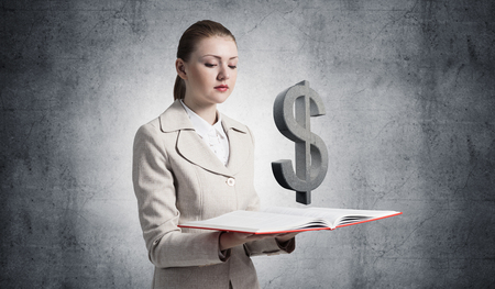 Photo pour Businesswoman with dollar sign above opened notebook. Investment and money saving services. Elegant young woman in white business suit on background of grey wall. Financial company advertising. - image libre de droit