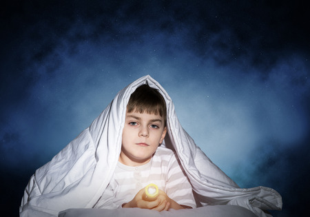 Photo pour Serious child with flashlight hiding under blanket. Attentive kid lying in his bed at home. Fear to sleep in darkness at night. Portrait of little boy in pajamas on background of deep starry sky. - image libre de droit