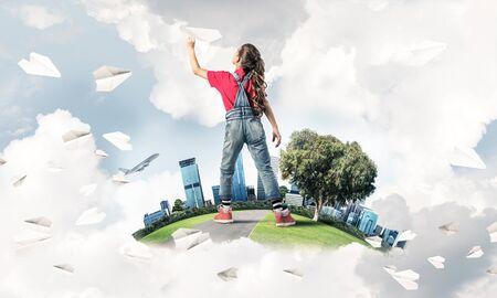 Foto de Cute kid girl on city floating island throwing paper plane - Imagen libre de derechos