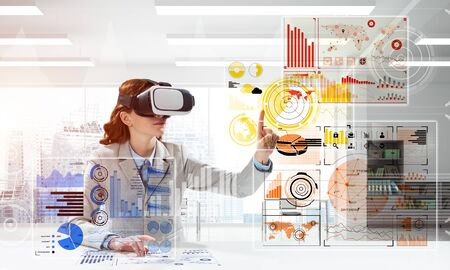 Photo pour Business woman in suit using virtual reality goggles while sitting inside bright office building. Concept of modern technologies for business needs. - image libre de droit