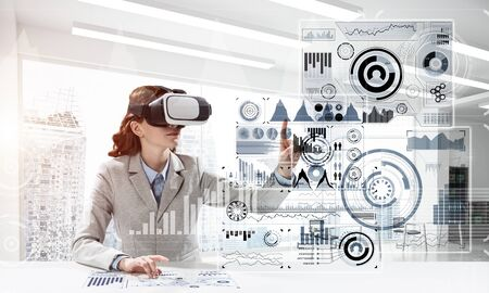 Photo pour Portrait of confident and successful business woman in suit sitting inside office building with digital media interface and using virtual reality headset - image libre de droit