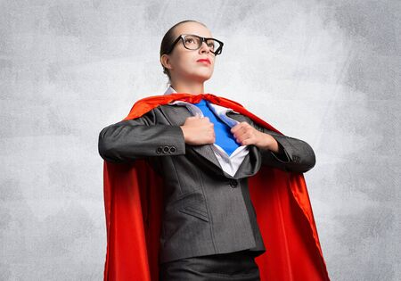 Photo pour Attractive young business lady in red hero cape on grey wall background. Portrait of business woman super heroine. Career development and leadership. Confident super woman ready for new challenges. - image libre de droit