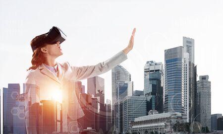 Photo pour Double exposure of businesswoman wearing virtual reality glasses and modern cityscape - image libre de droit