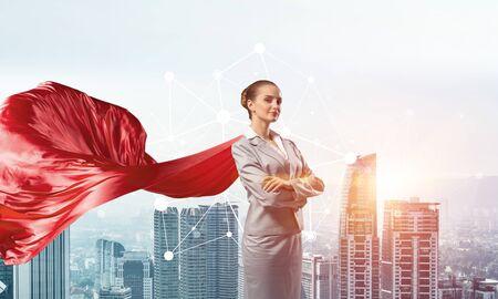 Photo pour Young confident businesswoman wearing red cape against modern city background - image libre de droit