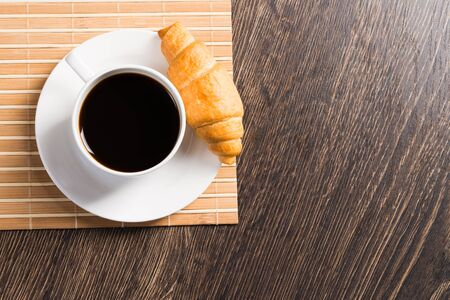 Cup of espresso coffee on wooden table. Top view white porcelain cup and delicious croissant on saucer. Close up fresh and aromatic hot drink in cafe. Morning breakfast and coffee time concept.