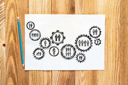 Photo pour Corporate HR management pencil hand drawn with group of rotating gears and cogs. Business team building sketch on wooden surface. Top view of workplace with paper and pencil lying on wooden desk. - image libre de droit