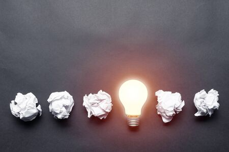 Photo for Lightbulb and crumpled white paper balls on black background. Successful solution of problem. Think outside the box. Business motivation with copy space. Genius idea among failing ideas metaphor. - Royalty Free Image