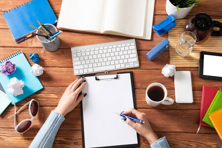 Photo pour Businesswoman writing on white paper with pen at desk. Business research and education. Flat lay office workplace with female hands. Digital technology and coworking space. Female student taking notes - image libre de droit