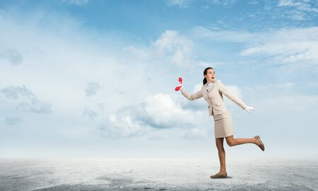 Woman runs away from something with vintage red phone. Scared secretary with telephone on background blue sky. Hotline telemarketing and communication. Professional business assistance and support