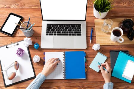 Photo pour Business woman writing in notebook at office desk. Online business learning and education. Flat lay office workplace with female hands, laptop and documents. Digital technology and coworking space - image libre de droit