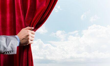 Photo pour Human hand opens red velvet curtain on blue sky background - image libre de droit