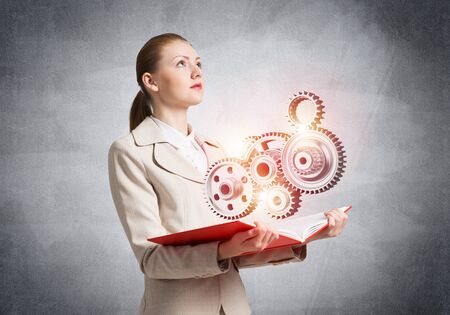 Photo pour Woman showing abstract mechanism with cogwheels on open book. Construction and manufacturing. Mechanical technology machine engineering. Woman in white business suit on background of grey wall. - image libre de droit