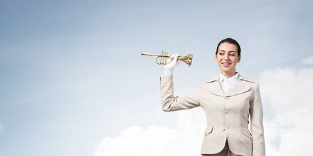 Beautiful woman holding trumpet brass near ear and listening. Young businesslady in white business suit and gloves posing with music instrument on blue sky background. Business concept with musician