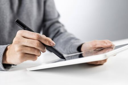 Foto de Businesswoman using tablet computer for news read. Close-up of female hands holding tablet device at office desk. Online business statistics and analytics. Modern workplace in innovate company - Imagen libre de derechos