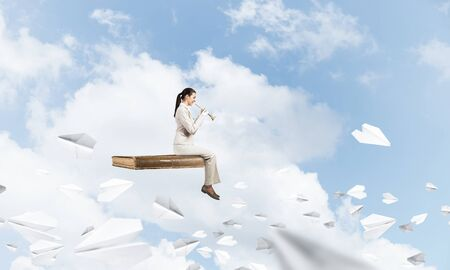 Photo pour Young woman playing trumpet and flying on book in blue sky. Girl in white business suit posing with music brass instrument. Imagination and inspiration. Business education concept with paper planes. - image libre de droit