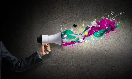 Businessman hand holding megaphone on wall background. Colorful paint splash flying out from loudspeaker. Event announcement and business advertisement. Social media broadcasting and online streaming